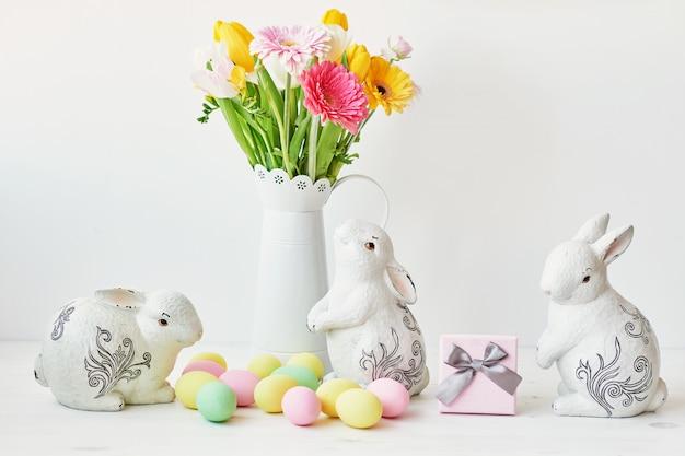 Conejito de pascua y huevos de pascua en la mesa de la cocina. conejo blanco sentado en la mesa con ramo de tulipanes y cresta y huevos coloridos.