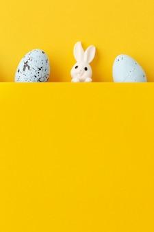 Conejito de pascua con huevos sobre fondo amarillo con espacio de copia