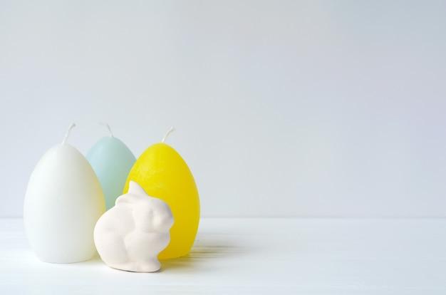Conejito de pascua con velas en forma de huevo en blanco con copyspace