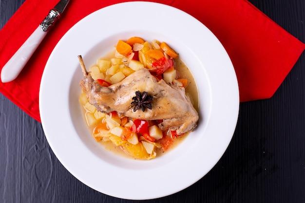 Conejo al horno con verduras en un plato blanco