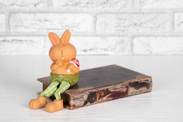 Conejo de juguete de cerámica decorativa se asienta sobre un libro antiguo