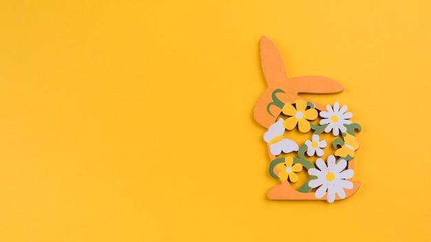 Conejo de madera con flores en mesa amarilla