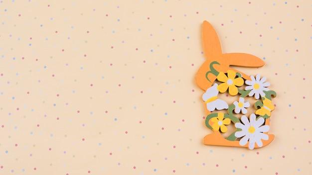 Conejo de madera con flores en mesa beige.