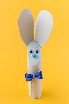 Conejo de madera con orejas de papel y pajarita.