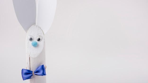 Conejo de madera con orejas de papel sobre fondo blanco