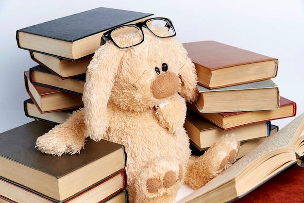 Un conejo de peluche con gafas se sienta en pilas de libros y lee un libro.