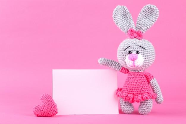 Conejo de punto en vestido rosa. decoración del día de san valentín. juguete de punto, amigurumi. tarjeta de felicitación del día de san valentín.