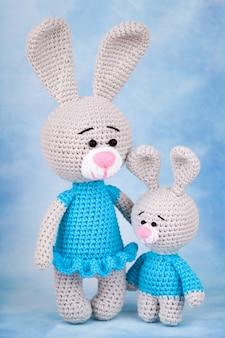 Conejos de punto - madre e hijo con regalos y flores.