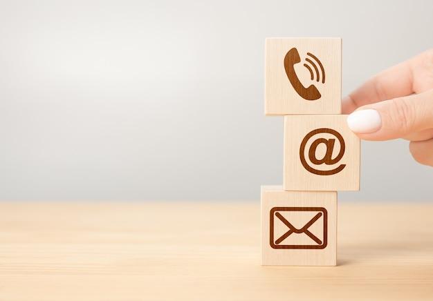 Conexión comercial en contacto con nosotros y el concepto de servicio al cliente del centro de llamadas, icono de teléfono móvil, sobre de correo electrónico, teléfono y dirección de correo electrónico. asimiento de la mano bloque de madera con símbolo de contacto