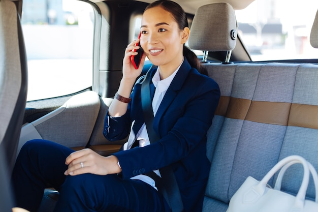 Conexión móvil. bonita mujer positiva respondiendo a la llamada mientras está en el coche.
