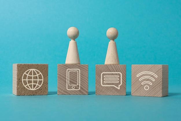 Conexiones digitales red internet figuras y bloques de madera con iconos sobre fondo azul.
