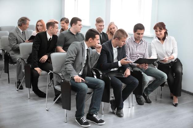 Conferencia de negocios. grupo de gente de negocios en ropa formal sentados en las sillas en la sala de conferencias