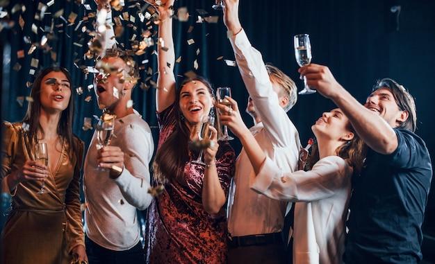 El confeti está en el aire. grupo de amigos alegres celebrando el año nuevo en el interior con bebidas en las manos.