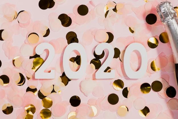 Confeti y botella de champagne en la fiesta de año nuevo