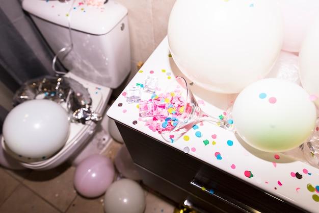 Confeti cayendo del vaso de martin con globos en el escritorio en el baño