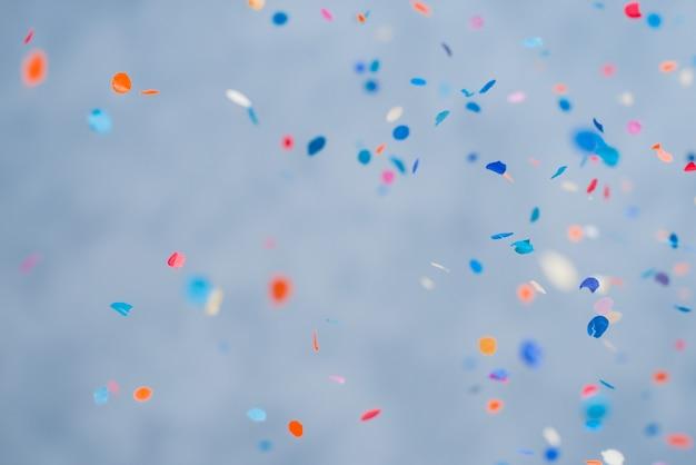 Confeti de colores cayendo sobre un fondo azul