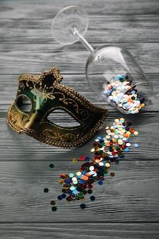 Confeti colorido caído de la copa de vino con máscara de carnaval de disfraces máscara en mesa de madera