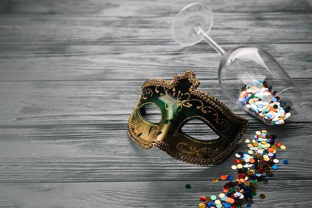 Confeti colorido caído de la copa de vino con máscara de carnaval sobre fondo con textura de madera