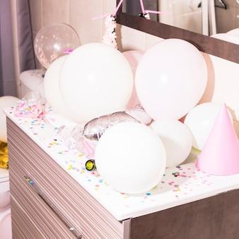 Confeti colorido y globos blancos en el escritorio de madera
