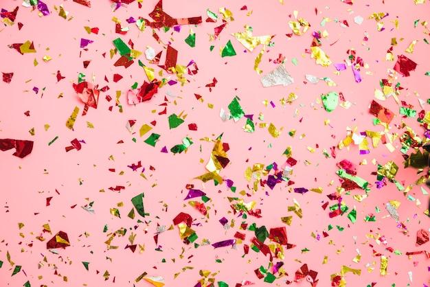 Confeti colorido sobre fondo rosa