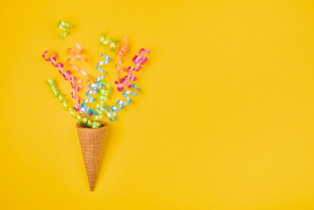 Confeti en cono de helado con espacio de copia sobre fondo amarillo
