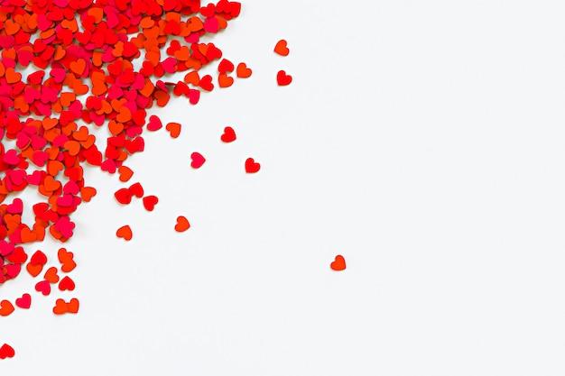 Confeti de corazones rojos. dispersión frontera arrinconada sobre fondo blanco. ilustración de renderizado 3d
