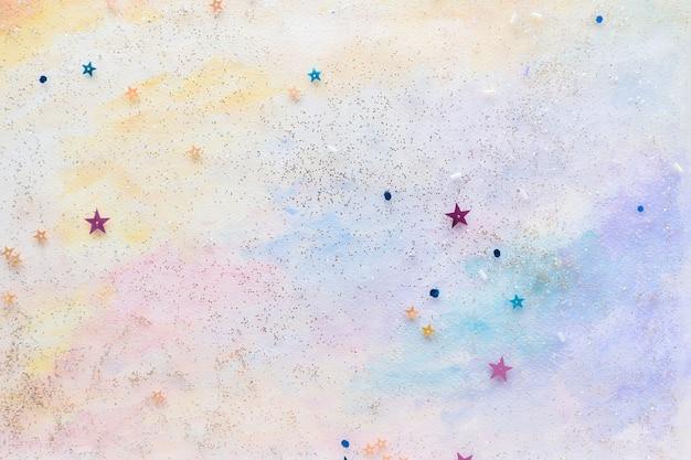 Confeti estrella reluciente sobre fondo acuarela pastel abstracto colorido