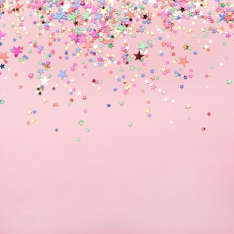 Confeti de estrellas coloridas sobre fondo rosa con espacio de copia