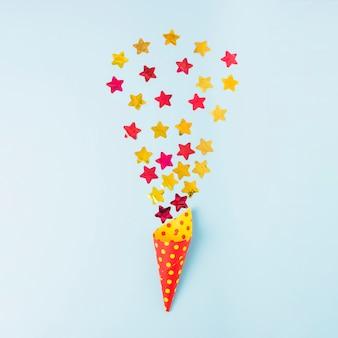 Confeti de forma de estrella sobre el cono de papel sobre fondo azul