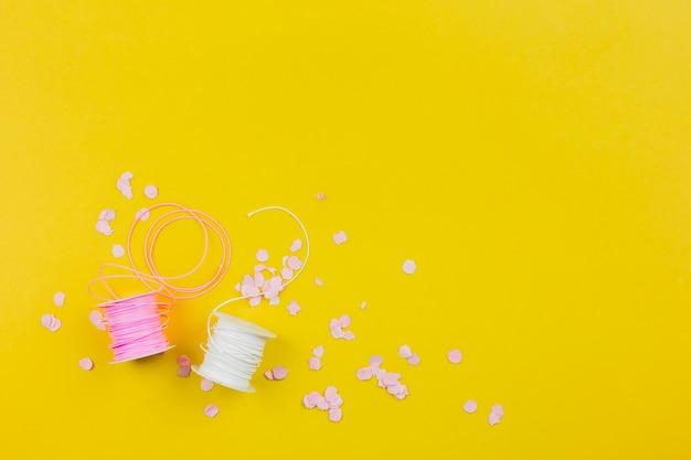 Confeti de papel con carrete rosa y blanco sobre fondo amarillo