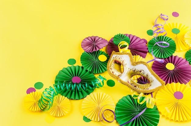 Confeti de papel de colores, máscara de carnaval y serpentina de colores sobre un fondo amarillo