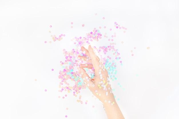 Confeti pastel perla brilla con mano de mujer