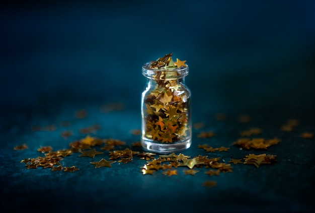 Confeti de purpurina dorada en la pequeña botella de vidrio