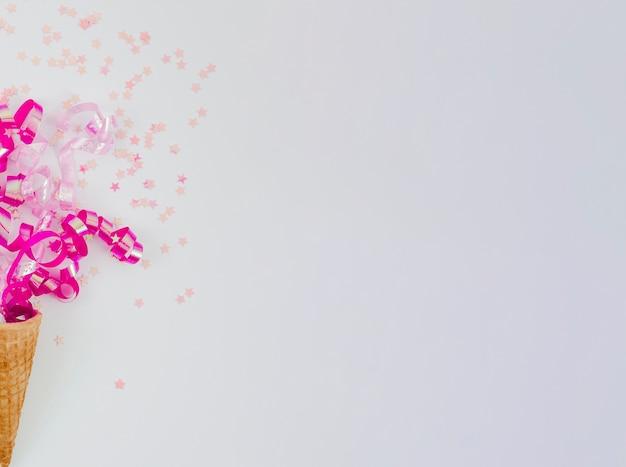 Confeti rosa en cono de helado con espacio de copia