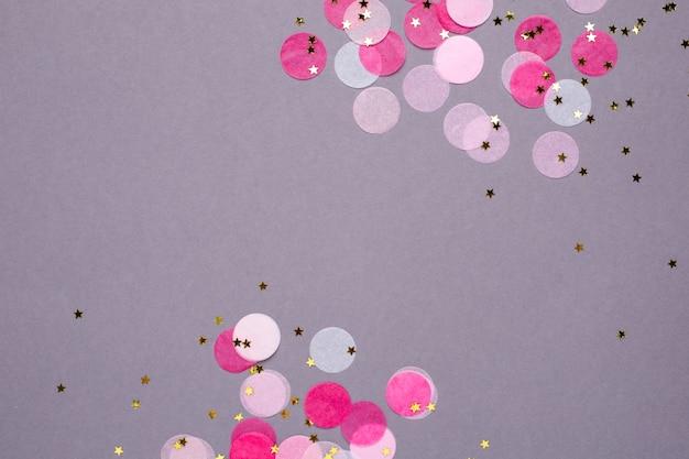 Confeti rosa con estrellas doradas sobre gris