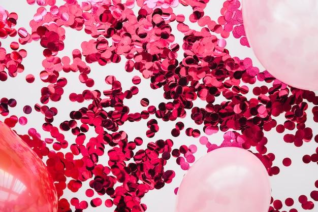 Confeti rosa y globos en disposición.