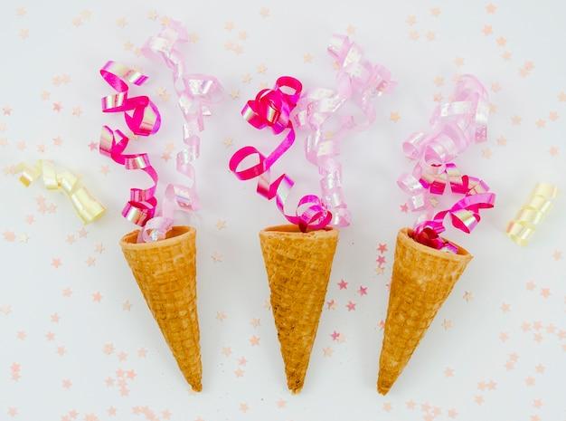 Confeti rosa sobre conos de helado