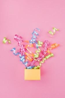 Confeti saliendo de la caja de regalo con fondo rosa
