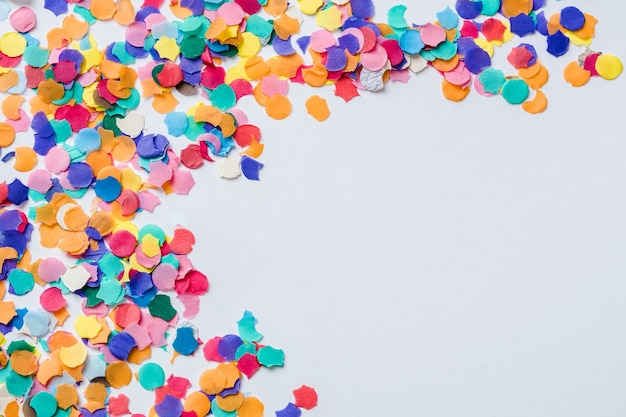Confettis de papel de colores sobre una superficie blanca