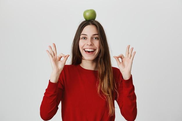 Confiada y emocionada, linda mujer sonriente mostrando un signo bien y sostenga la manzana verde en la cabeza