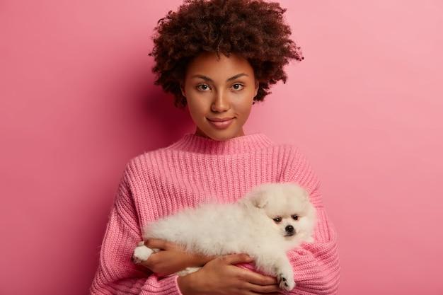 Confiada mujer afroamericana sostiene a un perro pequeño, acude al veterinario para obtener consejos sobre cómo alimentar al perro de pomerania