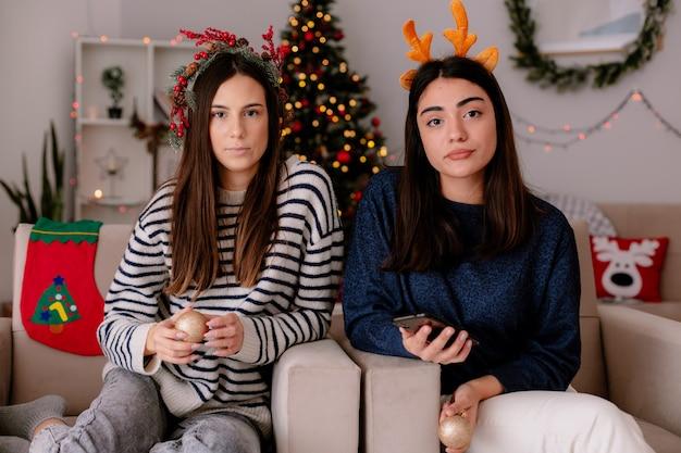 Confiadas chicas guapas con corona de acebo y diadema de renos sostienen adornos de bolas de cristal sentados en sillones y disfrutando de la navidad en casa