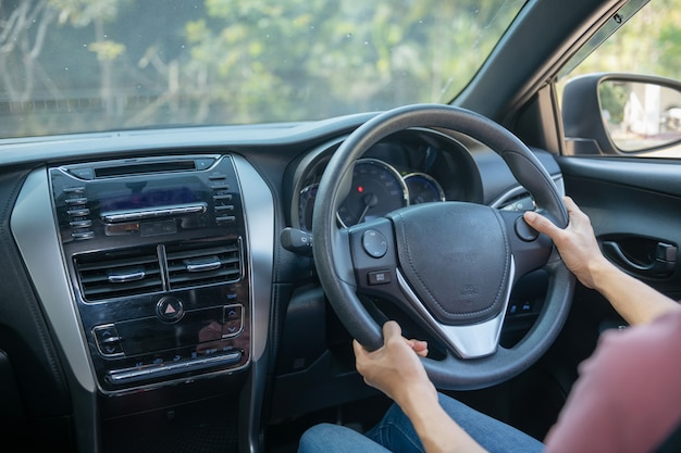 Confiado y hermoso. vista trasera de una mujer joven atractiva en ropa casual mirando por encima del hombro mientras conduce un coche. chica sosteniendo la mano en la rueda para manejar el coche, concepto de seguridad.