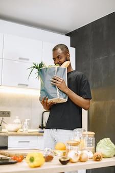 Confiado hombre africano hipster blogger grabando vlog sobre cocinar en cámara digital sentarse en una cocina