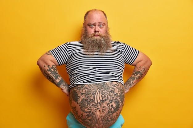 Confiado hombre serio de ojos azules con barba, tiene un gran abdomen, lleva un estilo de vida poco saludable, vestido con una camiseta de marinero a rayas, posa sobre una pared amarilla. chico regordete está seguro de sí mismo en el interior