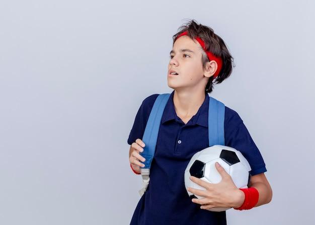 Confiado joven guapo deportivo vistiendo diadema y muñequeras y bolso trasero con aparatos dentales que sostienen la correa del bolso y el balón de fútbol mirando al lado aislado sobre fondo blanco con espacio de copia