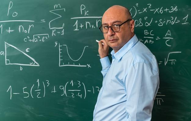 Confiado mirando al frente profesor de mediana edad con gafas de pie delante de la pizarra