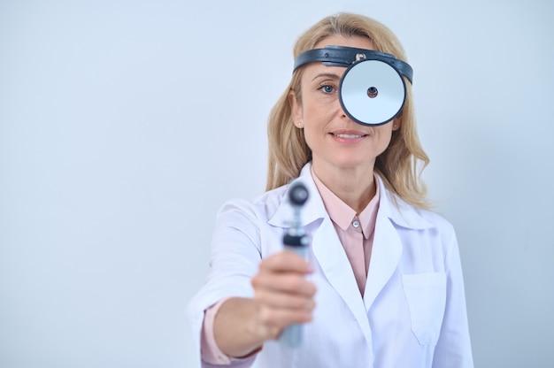 Confiado profesional médico caucásico con un otoscopio en la mano mirando a través del espejo de cabeza