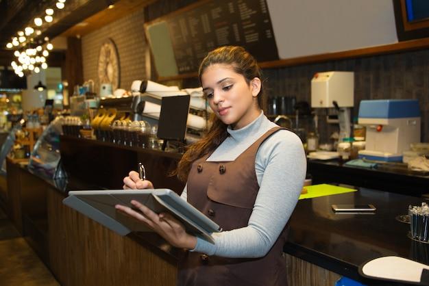 Confiado propietario del café escribiendo en el libro de registro