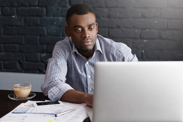Confiado y próspero joven gerente superior afroamericano vistiendo camisa formal tomando café